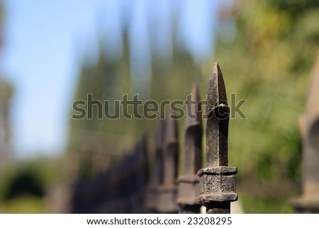 detail of a fence spike with blurred trees in the background (selective shallow DOF) - stock photo