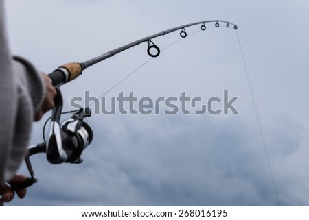 Detail of a Fishing Rod and Colorful Sky - stock photo