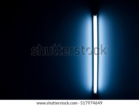 Detail of a fluorescent tube mounted on a wall, false green color light
