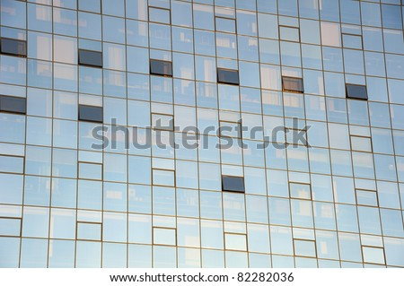 Detail of a glass-fronted office block with contents of offices faintly visible behind the glass. Suitable as abstract background.