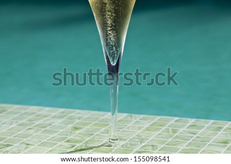 Detail of a glass of champagne by the pool / Champagne - stock photo