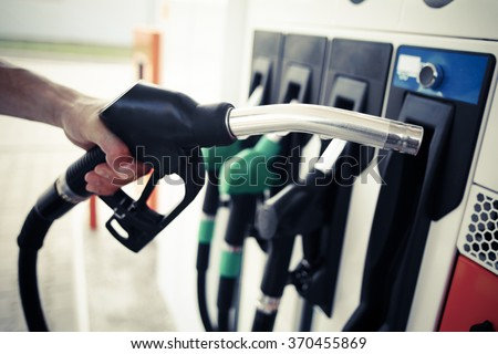 Detail of a hand holding a fuel pump at a station - stock photo