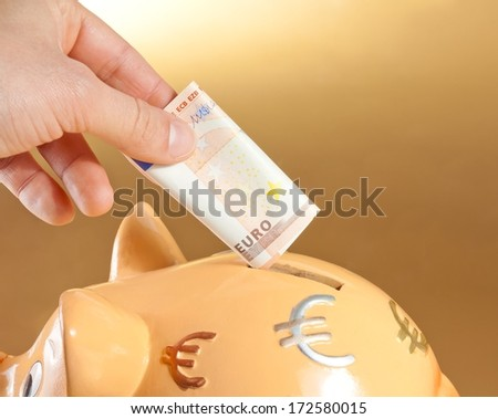 detail of a hand inserting a fifty euro banknote into a piggy bank, concept for business and save money on golden background - stock photo