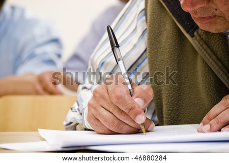 detail of a hand of man with red shirt  writing on a notebook with a blue pencil  and  blurred background - stock photo