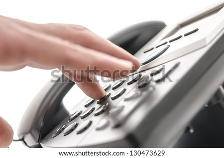 Detail of a hand pressing a button on a telephone keypad. With selective focus. - stock photo