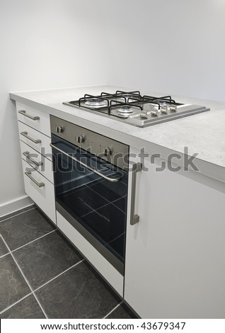 detail of a kitchen counter with oven and gas hob - stock photo