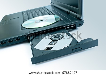 detail of a laptop with open and loaded dvd drive. Blue tone