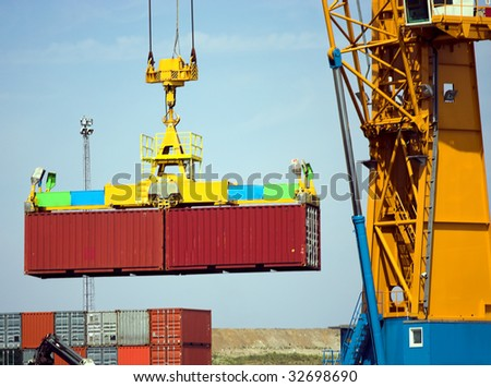 Detail of a large crane carrying containers into a freight ship (logos and brand names carefully removed) - stock photo
