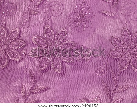 Detail of a lavender Oriental blouse sleeve with floral lace overlay with shiney threads woven through it. - stock photo