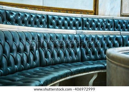 detail of a leather bench inside of the lecture hall with an antique elements nearby