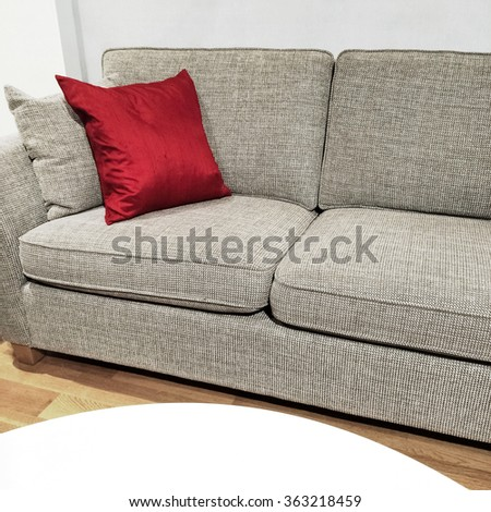 Detail of a living room. Sofa decorated with red cushion, and white coffee table. - stock photo
