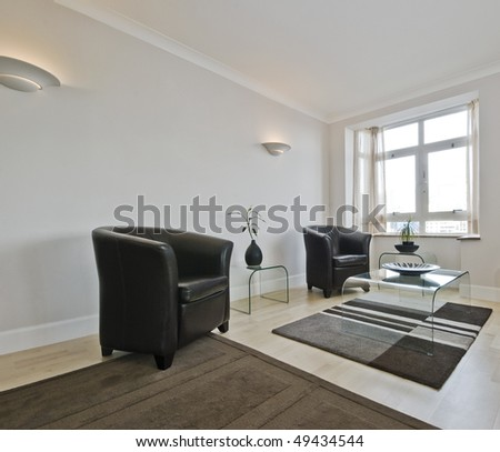 detail of a living room with bay window and leather armchairs - stock photo