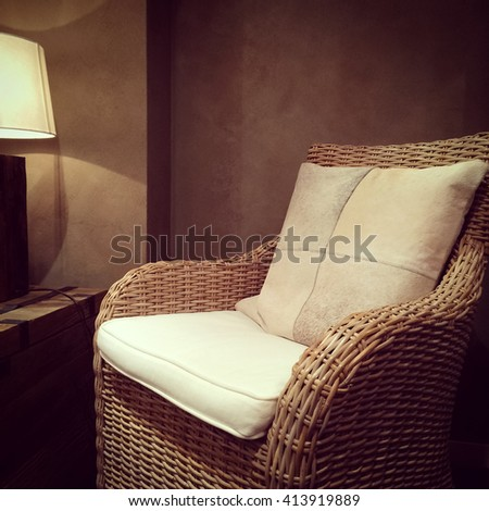 Detail of a living room with classic rattan armchair and cozy lamp. - stock photo