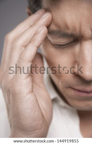 Detail of a male executive with fingers pressed to forehead against gray background - stock photo
