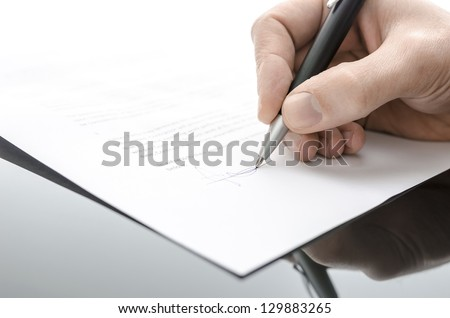Detail of a male hand signing a contract on a black table. - stock photo