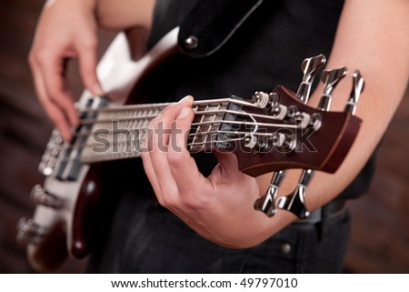 Detail of a man playing a Guitar. With the focus on the hand in the foreground.
