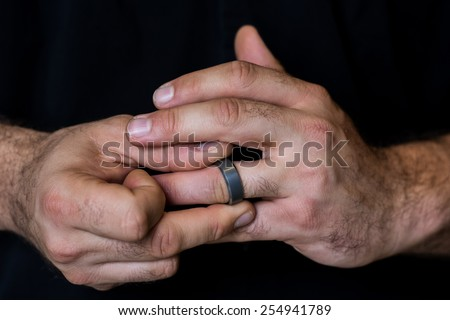 Detail of a man's hands fidgeting with a wedding ring