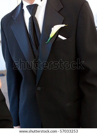 Detail of a man's suit or tux or tuxedo while getting married at a wedding. - stock photo
