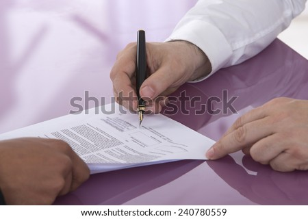 Detail of a man signing a paper Male finger showing where to sign - stock photo