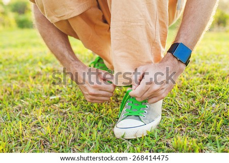Detail of a man tying his shoe strings with a smart watch on a man's wrist. Template for sport smartwatch app design - stock photo