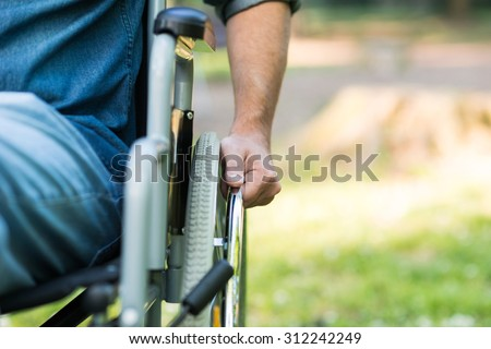 Detail of a man using a wheelchair in a park. Copy-space on the right side - stock photo