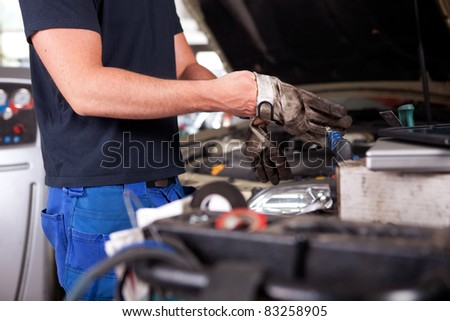 Detail of a mechanic putting on dirty work gloves - stock photo