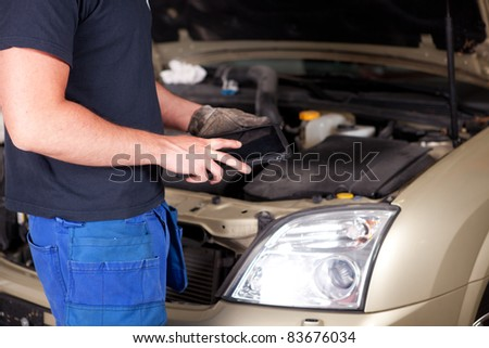 Detail of a mechanic with a digital tablet, car in background - stock photo