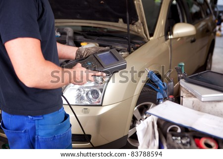 Detail of a mechanic with an electronic engine diagnostics tool - stock photo