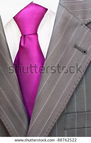 Detail of a men's striped business suit.Pink or violet  tie and a shirt - stock photo