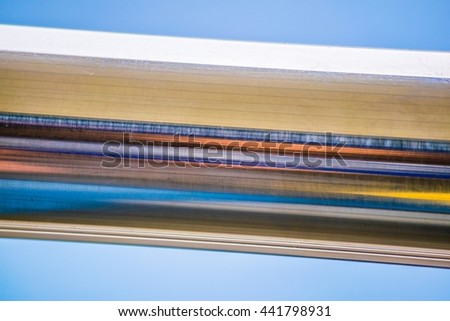 detail of a metal bar reflecting color strips on sun - stock photo