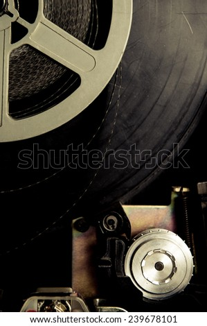 Detail of a 8mm vintage projector, with film and color effect - stock photo