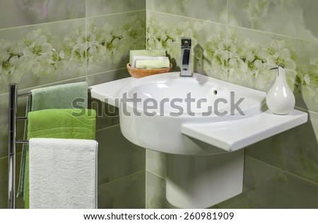 Detail of a modern bathroom with sink, towels and accessories for soap