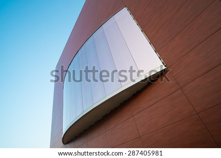 Detail of a modern facade with a large mirrored window - stock photo