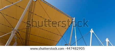 Detail of a modern tensile structure, membrane fabric roof with poles and steel cables, on a blue clear sky