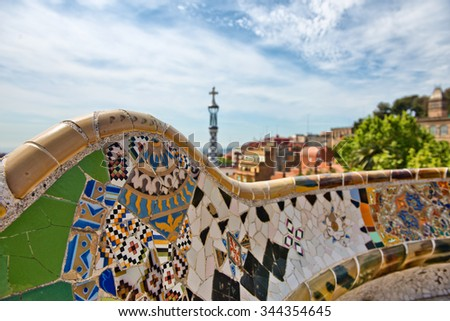Detail of a mosaic wall with colorful inlaid ceramic tiles on the main terrace, Parc Guell, Barcelona, Spain, designed by Antoni Gaudi - stock photo