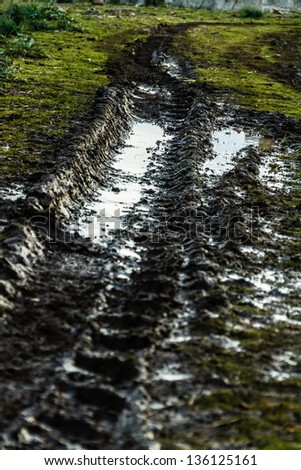 detail of a muddy track in a rural field with puddles - stock photo