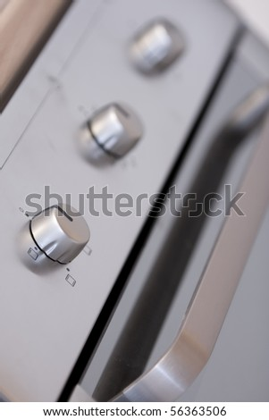 Detail of a new design stainless steel oven controls (selective focus on the first button) - stock photo