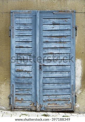 detail of a old rundown blue wooden door with blue flaking paint - stock photo