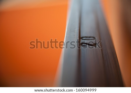 detail of a 20 on a polished wooden fixture  on an orange background and bokeh