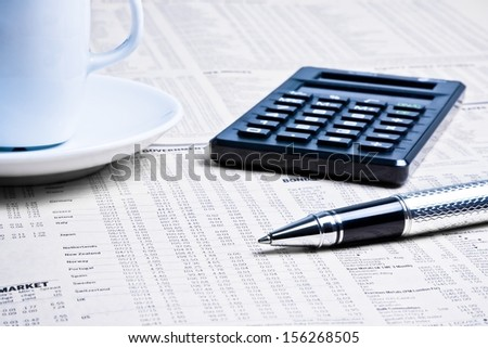 detail of a pen near a calculator with cup of coffee on financial newspaper under light tint blue - stock photo