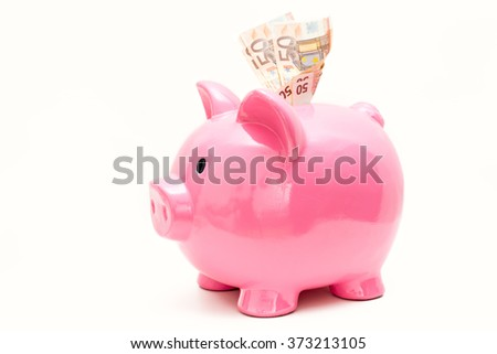 Detail of a piggy bank and several euro banknotes - stock photo