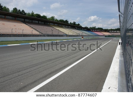 "detail of a racetrack named ""Hockenheimring"" in Southern Germany with tribune and street with lots ow wheel traces - stock photo"