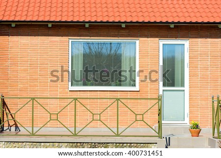 Detail of a red brick facade with a window and a patio door. Flowers and curtain in window, blinders down. Metal railing in front of balcony and a flowerpot at the stairs leading down. - stock photo