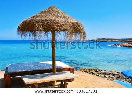 detail of a relaxing area in a Cala Conta beach in Ibiza Island, Spain, with a comfortable sunlounger and a rustic umbrella made of natural fibers - stock photo