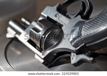 detail of a revolver on the metal desk