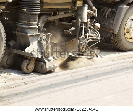Detail of a road sweeper cleaning a dust on  foot bath road - stock photo