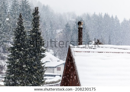detail of a roof covered with snow with a smoking chimney - stock photo