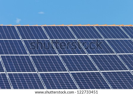 Detail of a roof with many solar panels in front of a blue sky - stock photo