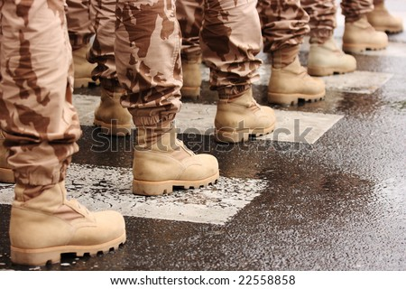 Detail of a row of soldiers wearing military boots on a zebra crossing - stock photo
