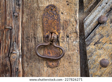 Detail of a rusty oval metal ring on an old brown wooden gate